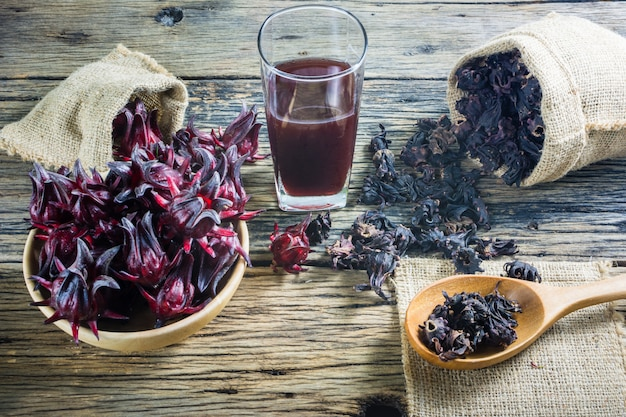 Fresh roselle, roselle dried and roselle juice on a wooden table.