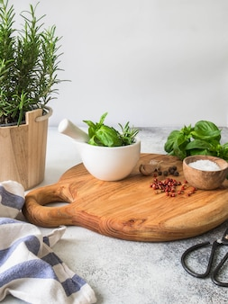 Fresh rosemary bush in wooden pots, twigs of fresh green basil, white mortar with pestle, salt and garlic on a round wooden tray top view.