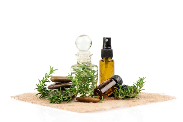Fresh rosemary flowers ,green leaves and extracted in the bottle isolated on white .