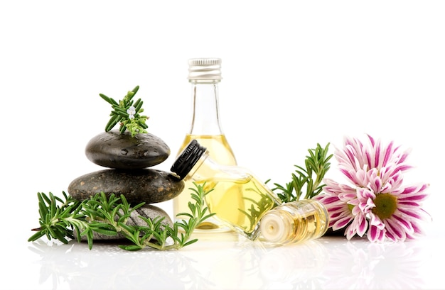 Fresh rosemary flowers ,green leaves and oil in the bottle isolated on white .