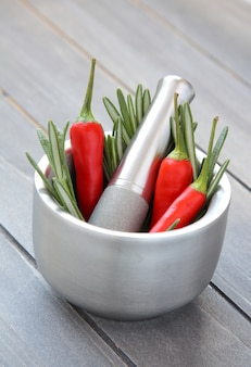 Fresh rosemary herb and red pepper in metal mortar with pestle on wooden background