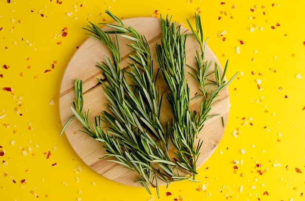 Fresh rosemary herb on the wooden board on yellow background