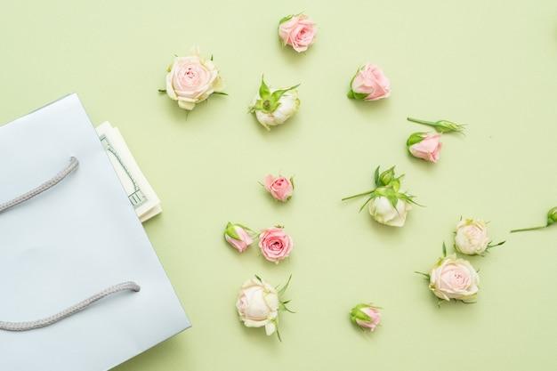Свежие розы на зеленой поверхности. подарочный пакет с деньгами. плоская планировка.