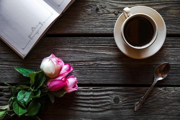Свежие розы с дневником и чашкой кофе на деревянном столе, вид сверху. цветы, горячий напиток