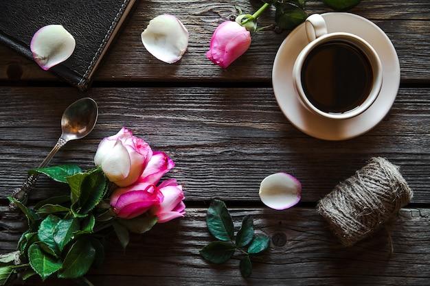 日記と木製のテーブル、上面図にコーヒーのカップと新鮮なバラ。花、温かい飲み物