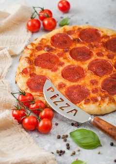 Fresh round baked pepperoni italian pizza with knife with tomatoes and basil on kitchen table background.