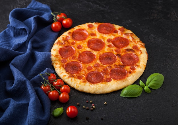 Fresh round baked pepperoni italian pizza with tomatoes with basil on black kitchen table background.
