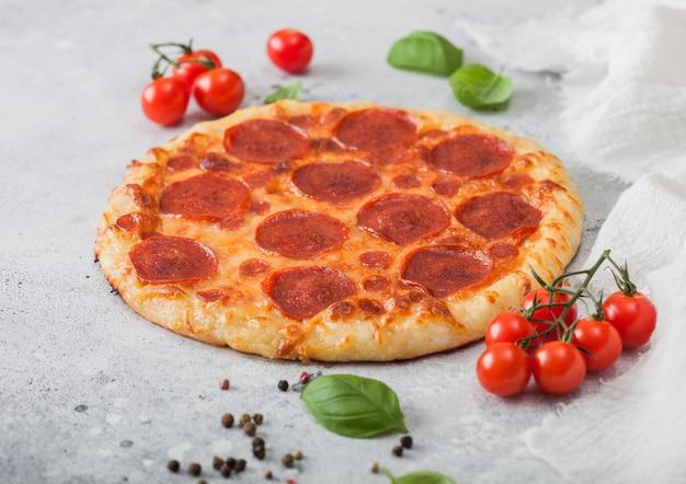 明るいキッチンテーブルの背景にバジルとトマトの新鮮な丸焼きペパロニイタリアンピザ。テキスト用のスペース