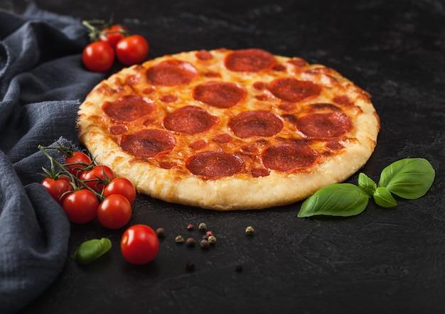 Свежая запеченная круглая итальянская пицца пепперони с помидорами и базиликом