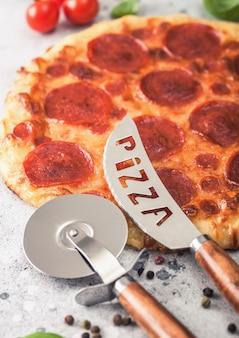 Свежая круглая запеченная итальянская пицца пепперони с колесным резаком и ножом с помидорами и базиликом на светлом фоне кухонного стола.