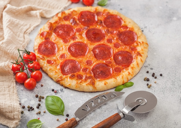 Fresh round baked pepperoni italian pizza with wheel cutter and knife with tomatoes and basil on light kitchen table background.