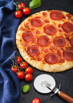 Fresh round baked pepperoni italian pizza with wheel cutter and tomatoes with basil on black kitchen table background.