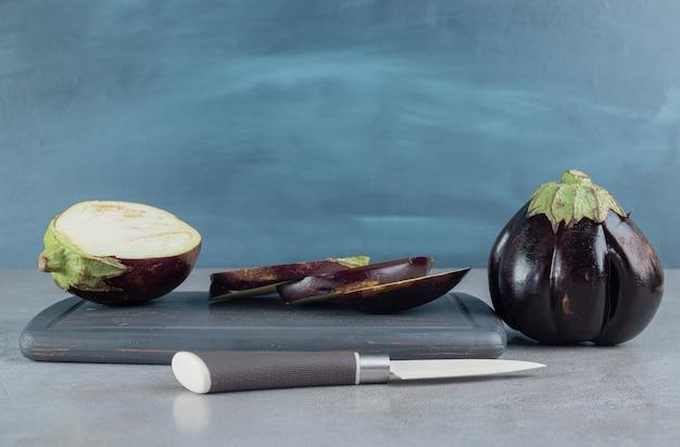 어두운 접시에 신선한 둥근 보라색 가지입니다. 고품질 사진