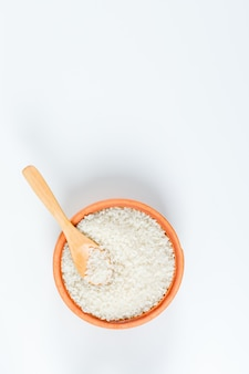 Свежий круглый рис в деревянной миске с деревянной ложкой сверху на белом фоне