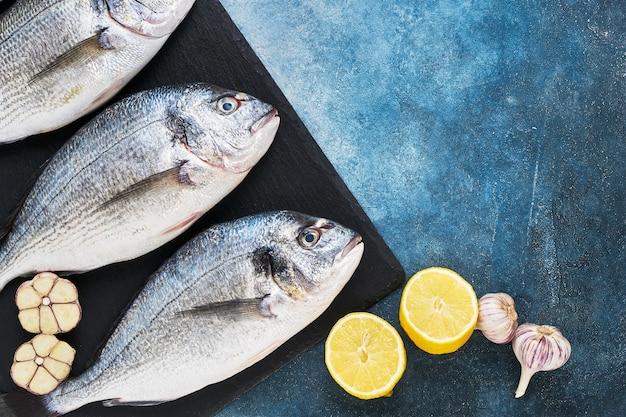 レモンとニンニクの健康食品のコンセプトトップビューコピースペースと青い背景に新鮮なロイヤルドラダ