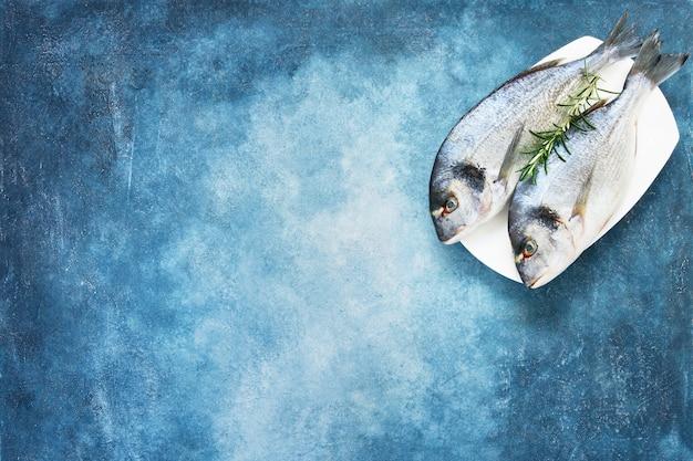 青いテーブルの上の新鮮なロイヤルドラダ。健康食品のコンセプト。上面図、コピースペース。