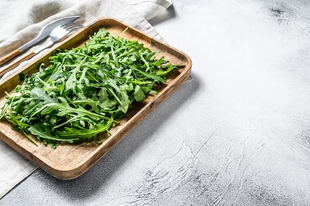 木製のボウルに新鮮なルッコラサラダ。灰色の表面。上面図。コピースペース