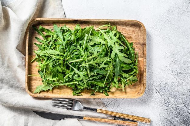 木製のボウルに新鮮なルッコラサラダ。灰色の表面。上面図