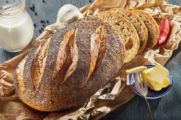 Свежий деревенский хлеб с нарезанными семенами мака и тесьмой из сливочного масла с кувшином из молока, перца и чеснока
