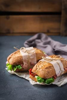Сэндвич из свежего ржаного хлеба с ветчиной, салатом и помидорами