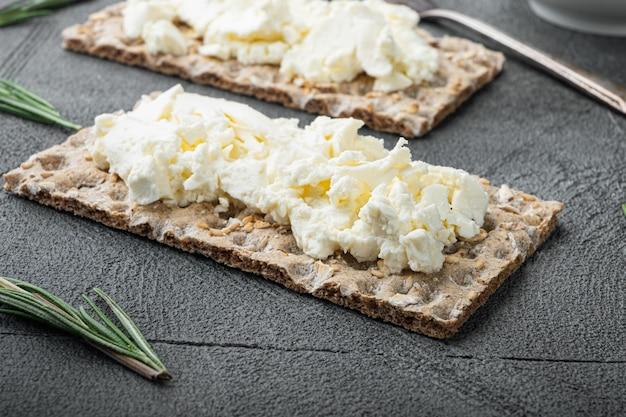 회색 돌 테이블에 크림 치즈 세트를 곁들인 신선한 호밀 크리스프 브레드