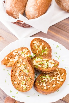 Fresh rye garlic croutons with dill on a plate on a wooden table