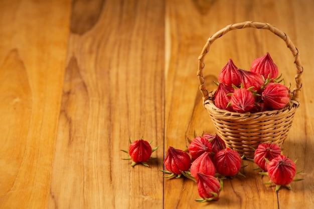 古い木の床に置かれた苗の新鮮なサブダリファハイビスカスまたはローゼル。