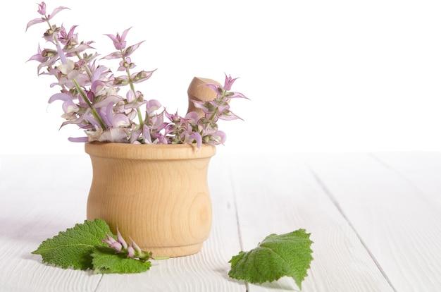 白い木製のテーブルの上の乳鉢で新鮮なセージ