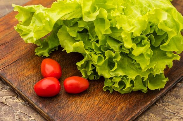 まな板の上に新鮮なサラダとレッドチェリートマト。ビタミンを含む食事療法