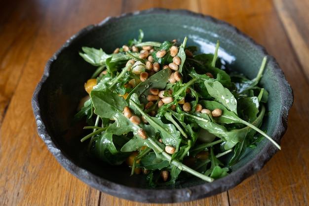 Fresh salad of arugula, pumpkin, apple and pine nut