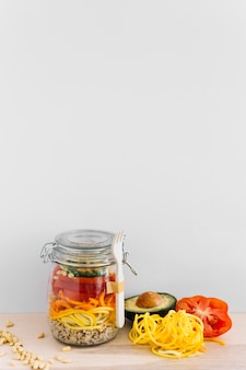 Fresh salad of avocado; tomato; corn seed and noodles in jar
