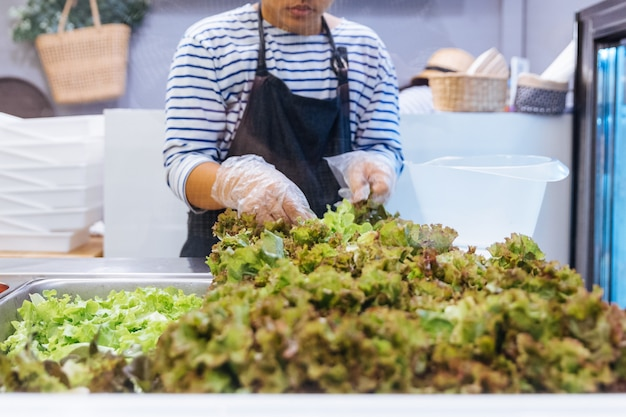Fresh salad bar counter with person's hands lifting lettuce into a plate for healthy and d