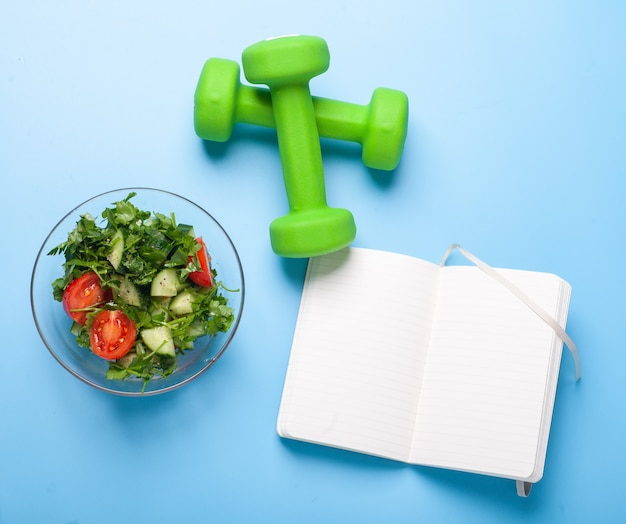 Fresh salad bowl, dumbbells and fitness diary with blank pages on bright blue background