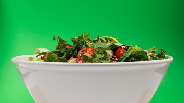 Fresh salad in bowl on green