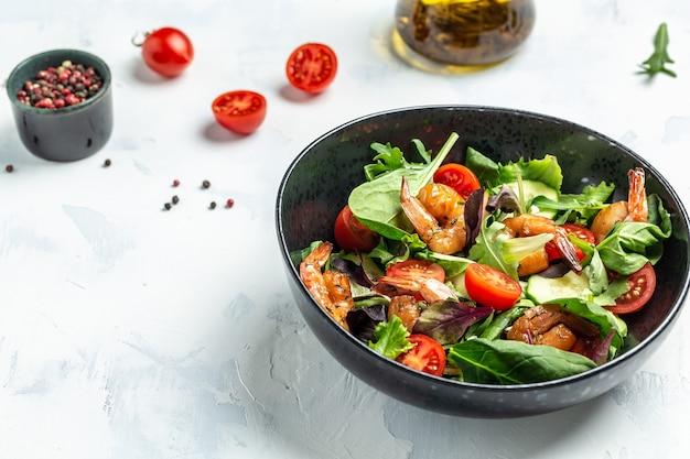 Свежий салат с авокадо и креветками в миске, вкусный завтрак или закуска на светлом фоне, вид сверху.