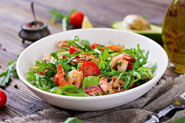 Fresh salad bowl with shrimp, tomato, avocado and arugula on wooden background close up.