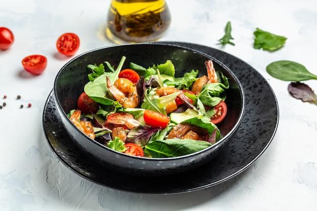 Свежий салат с копчеными креветками, помидорами черри, огурцом и смешанными листьями, здоровое питание. чистая еда. вид сверху.