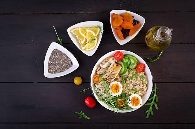 新鮮なサラダ。オートミール、鶏ムネ肉、トマト、レタス、マイクログリーン、ゆで卵の朝食ボウル。健康食品。ベジタリアン仏bowl。