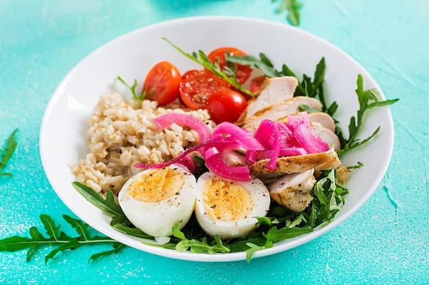 Свежий салат. чаша для завтрака с овсянкой, куриным филе, помидорами, красным луком и вареным яйцом. здоровая пища. вегетарианская чаша будды.