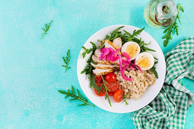 Fresh salad. breakfast bowl with oatmeal, chicken fillet, tomato, red onion and boiled egg. healthy food. vegetarian buddha bowl. top view, flat lay