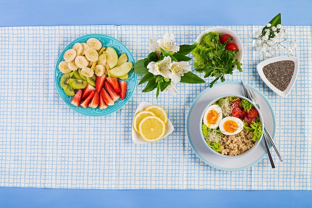 フレッシュサラダ。オートミール、トマト、レタス、マイクログリーン、ゆで卵の朝食用ボウル。健康食品。ベジタリアン仏丼。トップビュー、フラットレイアウト