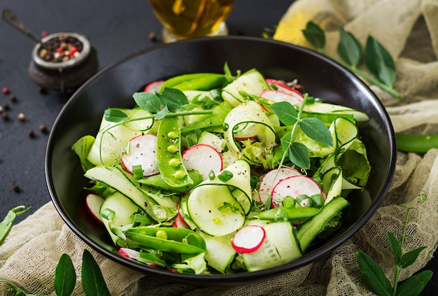 Fresh salad of cucumbers, radishes, green peas and herbs