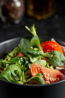 Fresh salad in dark bowl close-up