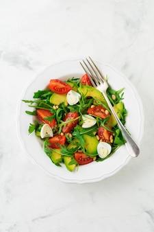 가벼운 돌 배경에 arugula, 토마토, 아보카도, 올리브 오일, 견과류 및 메추라기 계란에서 신선한 샐러드