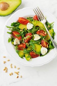 ルッコラ、トマト、アボカド、オリーブオイル、ナッツ、ウズラの卵のフレッシュサラダを軽い石の表面に。セレクティブフォーカス。上面図。