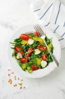 Свежий салат из рукколы, помидоров, авокадо, оливкового масла, орехов и перепелиных яиц на светлой каменной поверхности