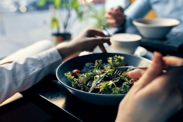 プレートの新鮮なサラダおいしい食べ物ダイエットフォークを手に女性の手カフェ