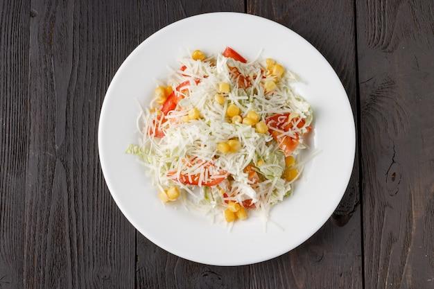 Свежий салат в деревянной тарелке на деревянный стол