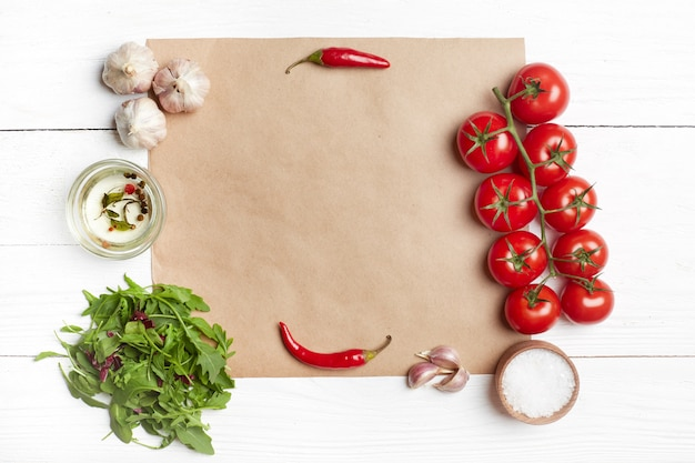 Fresh salad ingredients on brown paper. top view, flat lay, copy space, white wooden table.