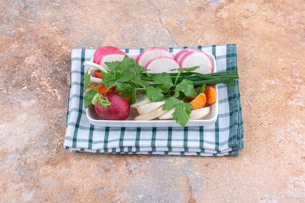 Gli ingredienti dell'insalata fresca impacchettano su un piatto su un asciugamano piegato sulla superficie di marmo